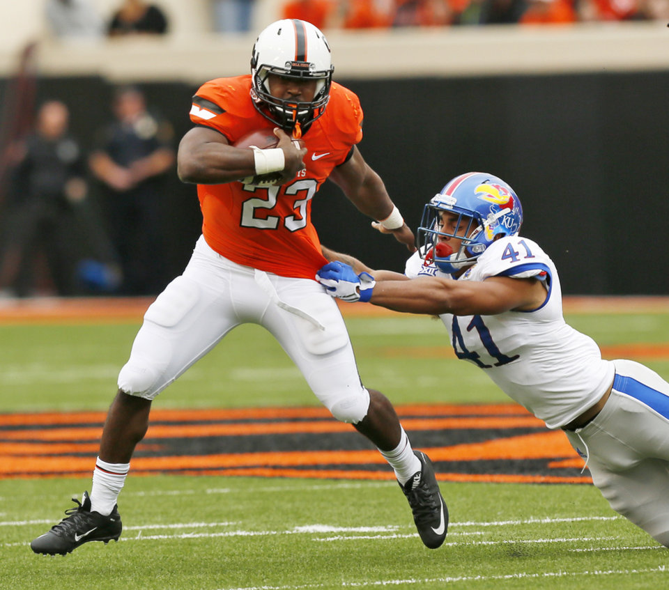 Photo - Oklahoma State's Rennie Childs (23) carries the ball against Kansas' Kendall Duckworth (41) during a college football game between the Oklahoma State University Cowboys (OSU) and the Kansas Jayhawks (KU) in Stillwater, Okla., Saturday, Oct. 24, 2015. Photo by Nate Billings, The Oklahoman
