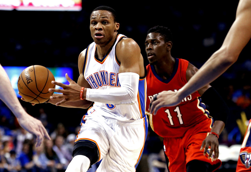 Photo - Thunder's Russell Westbrook (0) drives  past Pelican's Jrue Holiday (11) during the second half of an NBA basketball game between the Oklahoma City Thunder and the New Orleans Pelicans at Chesapeake Energy Arena on Dec. 21, 2014 in Oklahoma City, Okla. Photo by Steve Sisney, The Oklahoman