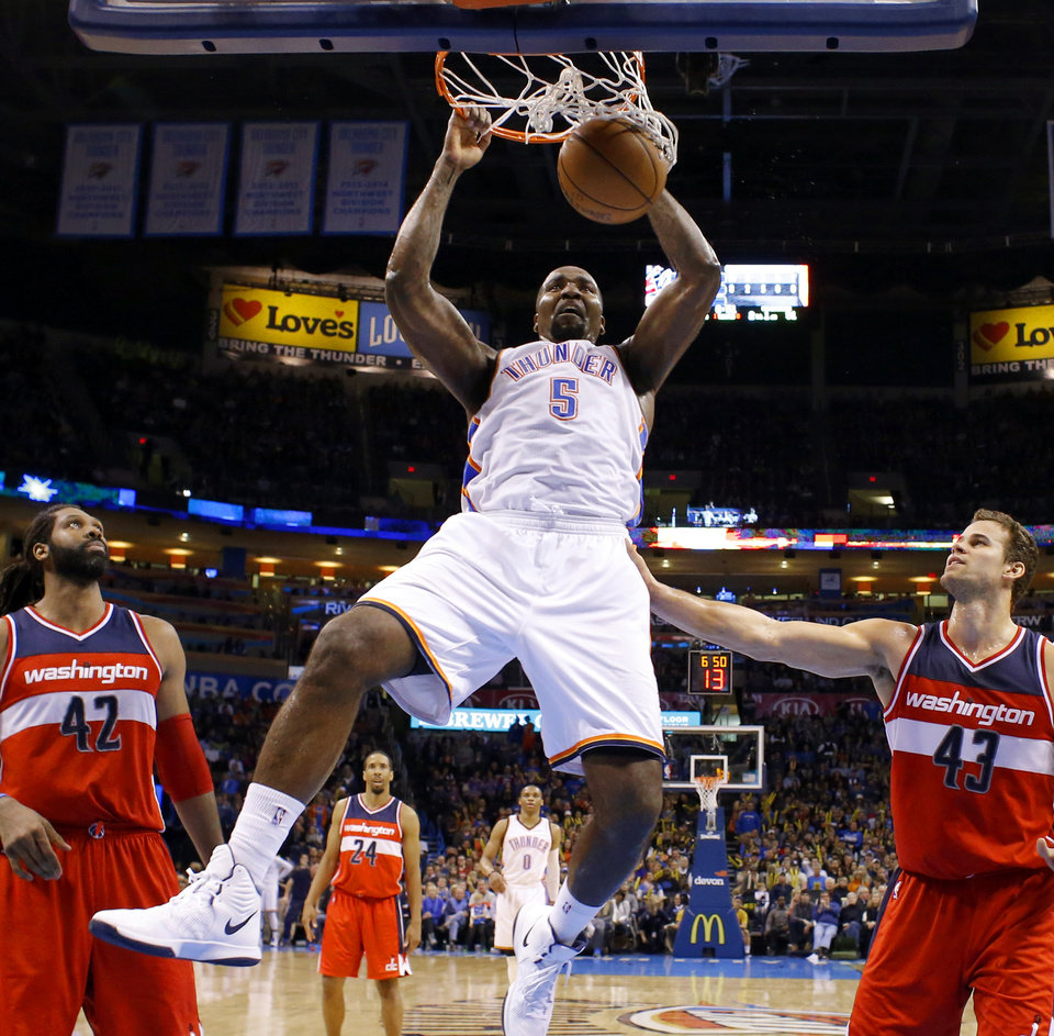 Photo - Oklahoma City's Kendrick Perkins (5) dunks between Washington's Nene Hilario (42) and Kris Humphries (43) during an NBA basketball game between the Oklahoma City Thunder and the Washington Wizards at Chesapeake Energy Arena in Oklahoma City, Friday, Jan. 2, 2015. Photo by Bryan Terry, The Oklahoman