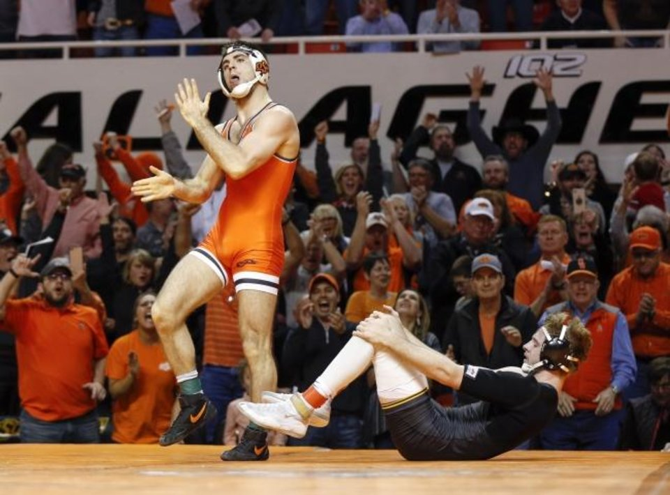 Photo -  Oklahoma State's Chandler Rogers, left, slaps his hands after pinning Iowa's Mitch Bowman in a 174-pound match on Sunday in Gallagher-Iba Arena. OSU won the dual 27-12 in front of a capacity crowd. [Nate Billings/The Oklahoman]