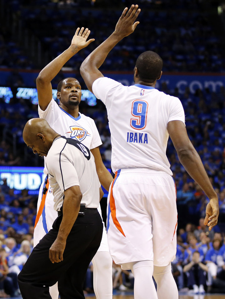 Photo - Oklahoma City's Kevin Durant (35) and Serge Ibaka (9) celebrate as official Tom Washington tries to get out of the way during Game 5 of the first round series between the Oklahoma City Thunder and the Dallas Mavericks in the NBA playoffs at Chesapeake Energy Arena in Oklahoma City, Monday, April 25, 2016. Photo by Nate Billings, The Oklahoman