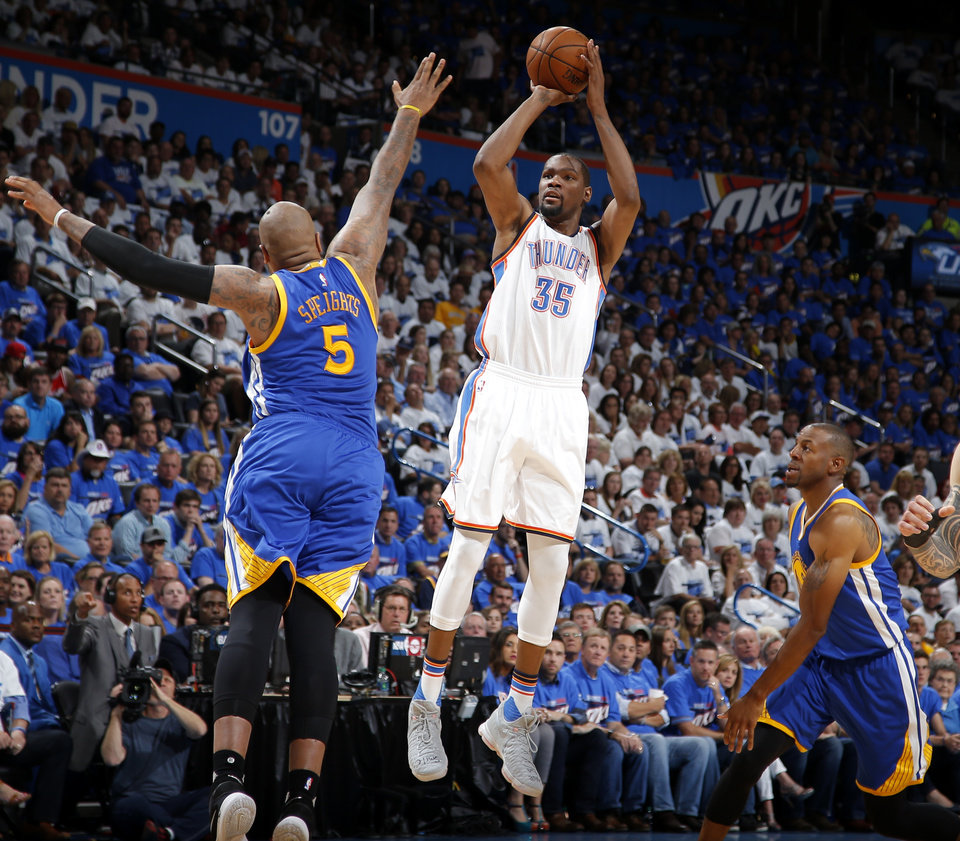 Photo - Oklahoma City's Kevin Durant (35) shoots from between Golden State's Marreese Speights (5) and Andre Iguodala (9) during Game 3 of the Western Conference finals in the NBA playoffs between the Oklahoma City Thunder and the Golden State Warriors at Chesapeake Energy Arena in Oklahoma City, Sunday, May 22, 2016. Photo by Bryan Terry, The Oklahoman