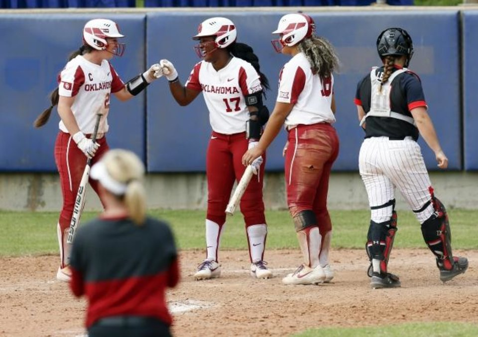 Photo -  Caleigh Clifton (20) bumps fists with Shay Knighten (17) after Jocelyn Alo (78) and Clifton scored in the sixth inning of OU's 8-0 win against Texas Tech in the Big 12 softball tournament Friday at USA Softball Hall of Fame Stadium. [Nate Billings/The Oklahoman]