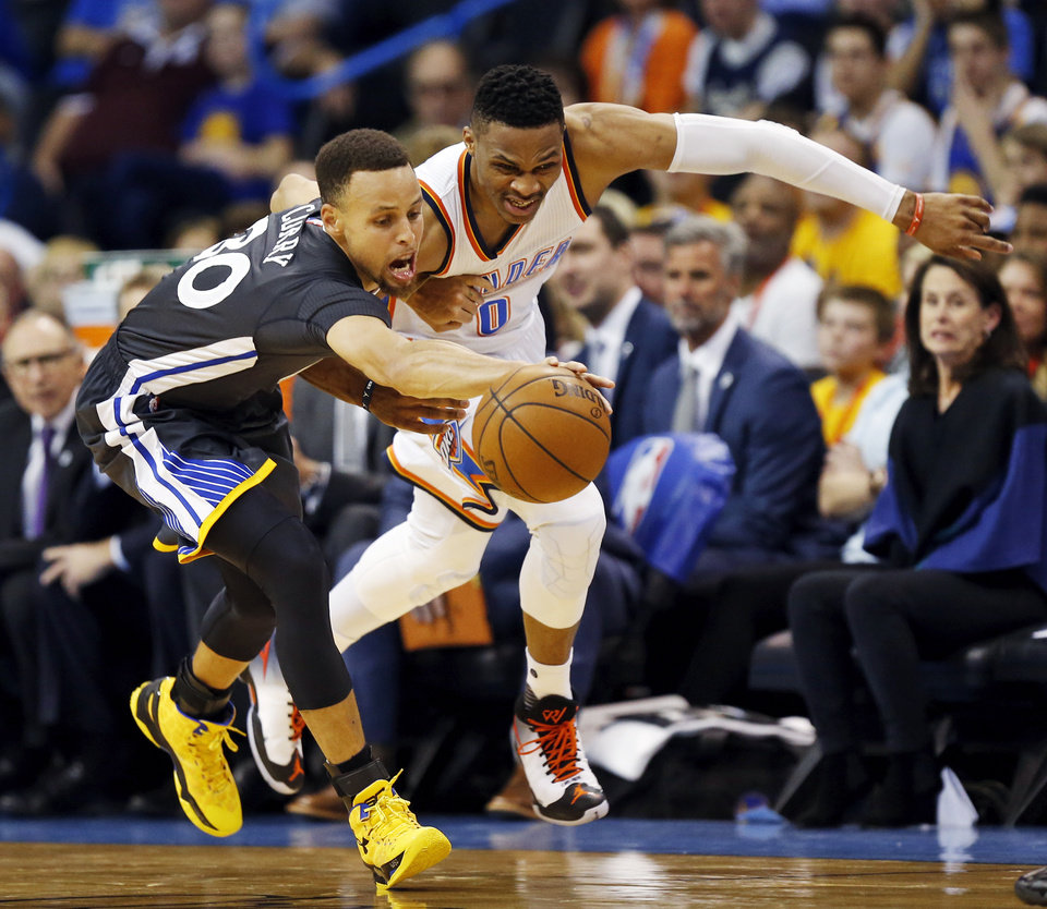 Photo - Oklahoma City's Russell Westbrook (0) and Golden State's Stephen Curry (30) chase the ball during an NBA basketball game between the Oklahoma City Thunder and the Golden State Warriors at Chesapeake Energy Arena in Oklahoma City, Saturday, Feb. 27, 2016. Golden State won 121-118 in overtime. Photo by Nate Billings, The Oklahoman