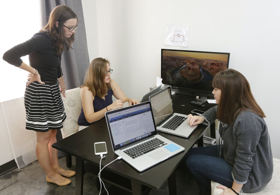 Photo -  Madison Baker, left, Emily Alkire and Melissa Megginson work together at Tailwind Interactive's office at 4010 N Lincoln Blvd. in Oklahoma City Sept. 15. [Photo by Paul Hellstern, The Oklahoman]
