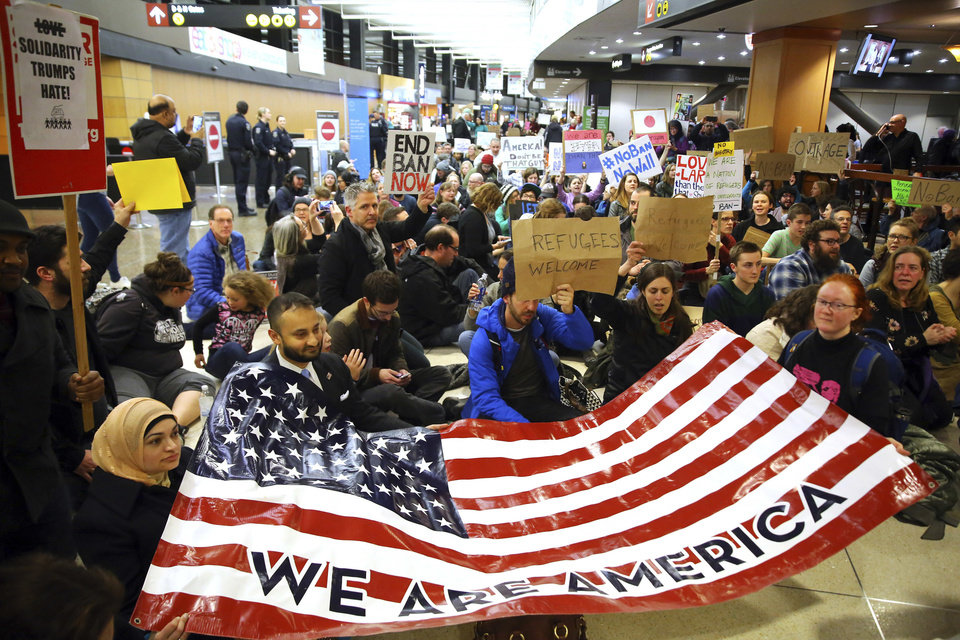 "Photo - Demonstrators sit down in the concourse and hold a sign that reads ""We are America,"" as more than 1,000 people gather at Seattle-Tacoma International Airport, to protest President Donald Trump's order that restricts immigration to the U.S., Saturday, Jan. 28, 2017, in Seattle. President Trump signed an executive order Friday that bans legal U.S. residents and visa-holders from seven Muslim-majority nations from entering the U.S. for 90 days and puts an indefinite hold on a program resettling Syrian refugees. (Genna Martin/seattlepi.com via AP)"