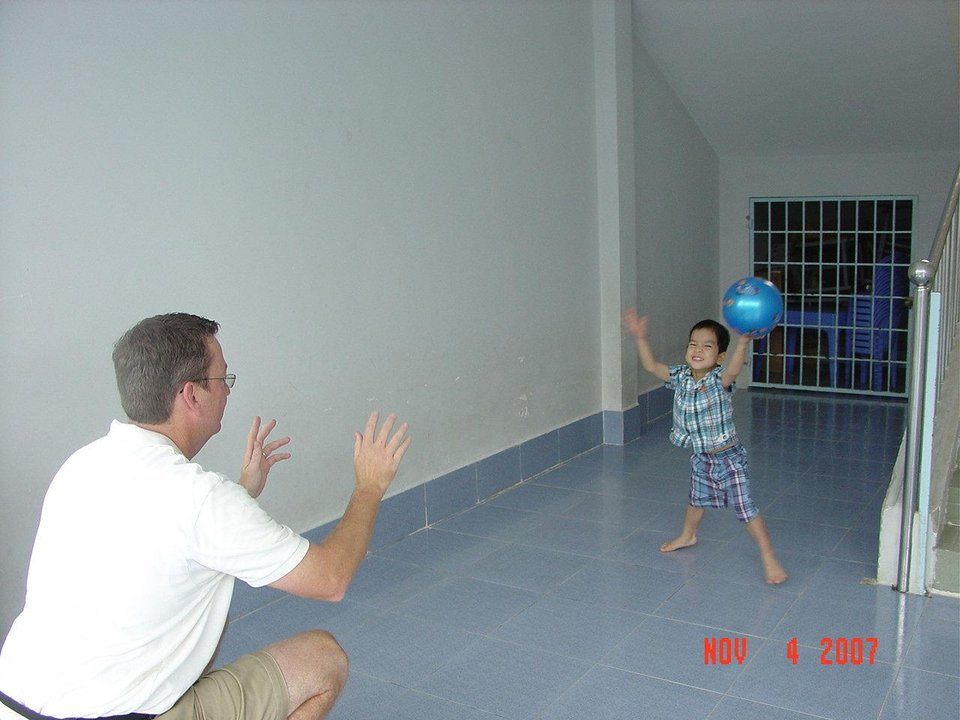 Photo - Austin Evans, then 3, plays ball with his new adoptive father Bill Evans at the ophanage in the Vihn Long Province of Vietnam where the boy lived the first few years of his life. Austin. Austin says his only real memory of being at the orphanage is of playing with a ball in his room. Austin is now 8 and raises money to send kids from that area to school. Photo provided.