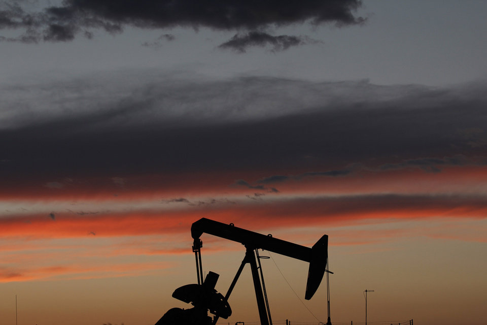 Photo -  The Oklahoma sunset is seen behind an oil pump in northwest Oklahoma City. [Photo by Doug Hoke, The Oklahoman]