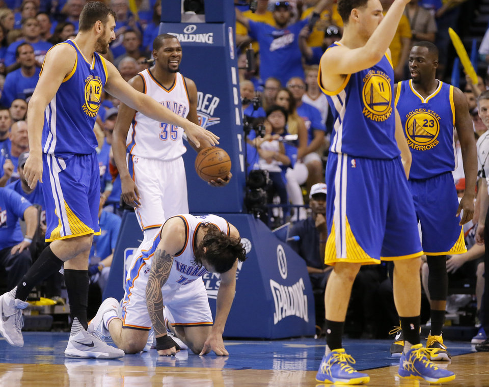 Photo - Oklahoma City's Steven Adams, center, bends over in pain after being kicked in the groin by Golden State's Draymond Green on Sunday in Game 3 of the Western Conference finals. Low blows are nothing new in the NBA, and most come with a penalty. (Photo by Bryan Terry, The Oklahoman)