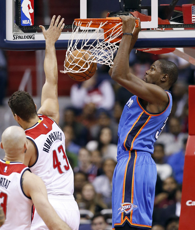 Photo - Oklahoma City Thunder forward Kevin Durant, right, dunks in front of Washington Wizards forward Kris Humphries during the first half of Tuesday's game in Washington. Durant suffered a pulled hamstring in the half. (AP Photo)