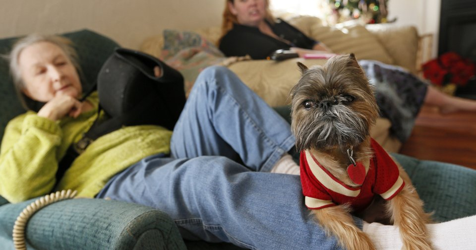 Trevor, a Brussels Griffon, sits on the leg of his owner, resident Cathi Doar, left, next to manager Lisa Schrameck  in the common area at Green Acres, 7601 SW 74.  NATE BILLINGS - The Oklahoman