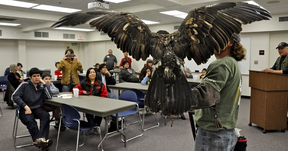 Above: Harley Coleman, an aviary assistant at the Grey Snow Eagle House, holds an eagle (also shown at left) Tuesday during a presentation for students in the Indian Education Program in the Putnam City School District. Photos by M. Tim Blake, for The Oklahoman