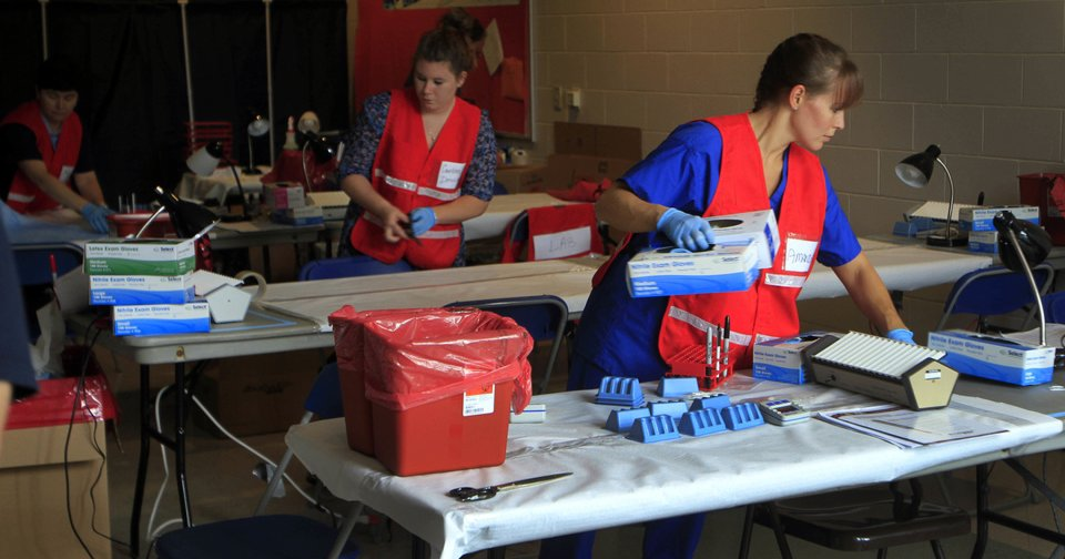 In this Aug. 11 file photo, employees of the New Hampshire state health department set up a temporary clinic at the the middle school in Stratham, N.H., to test hundreds of people for hepatitis C related to an outbreak at nearby Exeter Hospital. AP file photo  Jim Cole - AP file photo