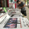 A vendor stocks bottles of soda at a newsstand with newspaper front page covers of the meeting in Singapore between U.S. President Donald Trump and North Korean leader Kim Jong Un in Beijing, China, Tuesday, June 12, 2018. China has suggested that the U.N. Security Council consider suspending or lifting sanctions against North Korea if the country is in compliance with U.N. resolutions and making progress in diplomatic negotiations. (AP Photo/Ng Han Guan)