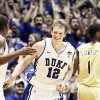 Photo - Duke's Kyle Singler (12) and Nolan Smith, left, react following Singler's basket against Georgia Tech during the second half of an NCAA college basketball game in Durham, N.C., Sunday, Feb. 20, 2011. Duke won 79-57. At right is Georgia Tech's Iman Shumpert (1). (AP Photo/Gerry Broome)