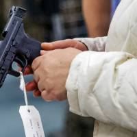 A customers takes a closer look at a handgun at H&H Shooting Sports in Oklahoma City, Okla. on Wednesday, March 18, 2020.  [Chris...