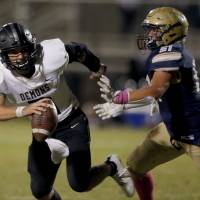 Perkins-Tryon's Austin Mages scrambles as he is pressured by Kingfisher's TJ Parker during the high school football game between Kingfisher and...