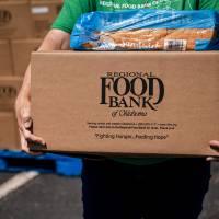 Katelyn Gleason-Dockery prepares to load a box of food into a clients car during the Regional Food Bank of Oklahoma food distribution event for...