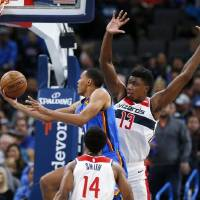 Oklahoma City's Darius Bazley (7) takes the ball to the basket between Washington's Thomas Bryant (13) and Ish Smith (14) in the third quarter...