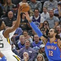 Oklahoma City Thunder center Steven Adams (12) defends against6 Utah Jazz guard Donovan Mitchell (45) in the first half of an NBA basketball game...