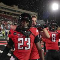 Texas Tech defensive back DeMarcus Fields (23) celebrates with his teammates after the Red Raiders' 34-27 win over West Virginia last Saturday....
