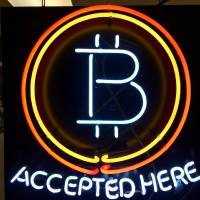 FILE - In this Feb. 7, 2018 file photo, a neon sign hanging in the window of Healthy Harvest Indoor Gardening in Hillsboro, Ore., shows that the business accepts bitcoin as payment. (AP Photo/Gillian Flaccus, File)