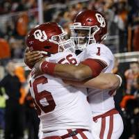 Oklahoma' quarterback Jalen Hurts, right, and center Creed Humphrey celebrate a touchdown catch by Hurts on a trick play against Okahoma State....