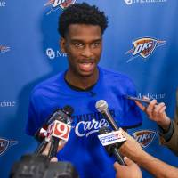 Oklahoma City Thunder's Shai Gilgeous-Alexander talks with the media after helping third grade students pick out books on the Rolling Thunder Book...
