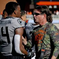 Oklahoma State head coach Mike Gundy talks with Oklahoma State's Jarrick Bernard (24) during the college football game between the Oklahoma State...