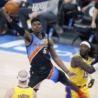 Oklahoma City's Hamidou Diallo (6) goes past Los Angeles' Montrezl Harrell (15) to score during an NBA basketball game between the Oklahoma City...
