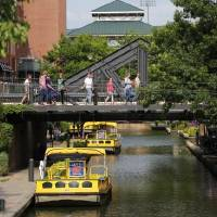 A lush tree canopy provides shade along the Bricktown Canal where water taxis travel between basements of century-old buildings that were opened...