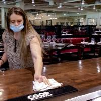 Bellini's Ristorante & Grill's general manager, Shawnna Underwood, cleans off the bar top Thursday. [Chris Landsberger/The Oklahoman]