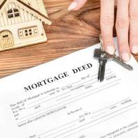 Female's hand giving mortgage deed and keys from house over table.