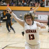 Photo -  Norman's Lainy Fredrickson waves to the crowd after making a shot in Friday's game against Norman North while Norman High students celebrate on the court behind her. [PHOTO BY BRYAN TERRY, THE OKLAHOMAN]