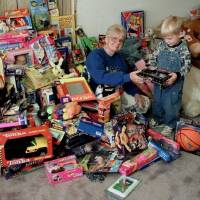 Red Andrews Christmas Dinner organizer Betty McCord and helper Joshua Looney, 3, are shown sorting through donated toys in this 1998 photo. [THE...