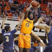 Oklahoma State's Isaac Likekele (13) passes the ball as Oral Roberts's Max Abmas (3) defends during an NCAA basketball game between the Oklahoma...