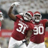Oklahoma's Jalen Redmond (31) and Neville Gallimore (90) celebrate during the Big 12 Championship Game on Saturday. The Sooners beat Baylor 30-23...