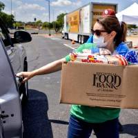 Katelyn Gleason-Dockery loads a box of food into a client's car Wednesday during a Regional Food Bank of Oklahoma food distribution event for...