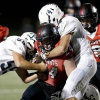 Minco players Cashus Burchfield, right, and Orlando Vazquez, far left, team up to bring down Crossings Christian's Jacob Snyder during a game last...