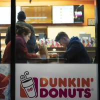In this Jan. 30, 2019, file photo customers sit inside a Dunkin' Donuts in New York. Dunkin' Brands Group Inc. reports financial results Thursday,...