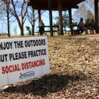 Sign at Whispering Heights Park in Edmond tells people to maintain social distancing Wednesday,  March 25, 2020.  [Photo by Doug Hoke/The Oklahoman]
