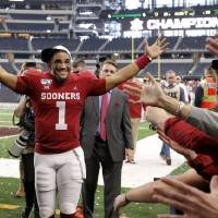 Oklahoma quarterback Jalen Hurts celebrates after the Sooners' Big 12 Championship victory over Baylor on Saturday in Arlington, Texas. Hurts and...