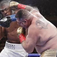 Andy Ruiz Jr. (right) and Anthony Joshua exchange punches during  the heavyweight championship match Saturday. Ruiz won in the seventh round