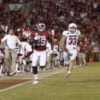 Oklahoma's Rhamondre Stevenson (29) caries the ball for a long touchdown in front of South Dakota's Jake Matthew (33) and Cameron Tisdale (5) in...
