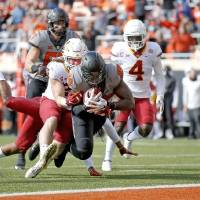 Oct 24, 2020; Stillwater, Oklahoma, USA;   Oklahoma State Cowboys player Jelani Woods (89) scores a touchdown as Iowa State Cyclones player Mike...
