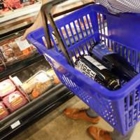 A shopper picks out meat in the butcher department while carrying bottles of wine in his basket inside the Homeland grocery store in Oklahoma...