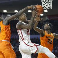 Oklahoma's Kristian Doolittle (21) goes to the basket between Oklahoma State's Isaac Likekele (13) and Kalib Boone (22) during a Bedlam college...