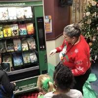 A book falls to the bottom of Oklahoma's first book vending machine on Friday at Charles Haskell Elementary in Edmond. The school purchased the...