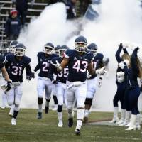FILE - In this Nov. 24, 2018, file photo, Connecticut linebacker Darrian Beavers (43) leads his team onto the field before the start of an NCAA...