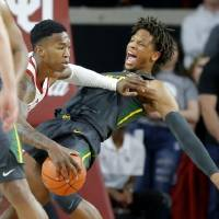 Oklahoma's Kristian Doolittle (21) tries to get past Baylor's Freddie Gillespie (33) during a men's NCAA basketball game between the University of...